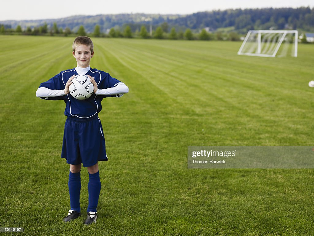 Boy (12-13) standing, holding football, on pitch : Stock Photo