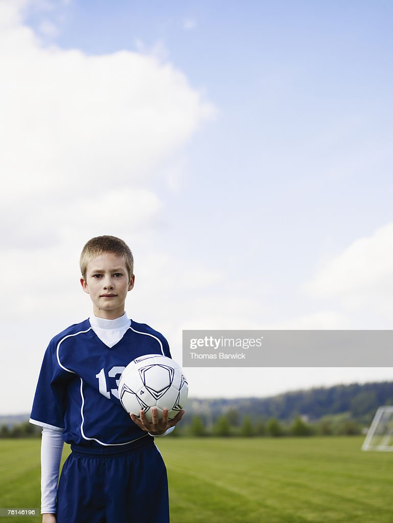 Boy (12-13) standing, holding football, on pitch, portrait : Stock Photo