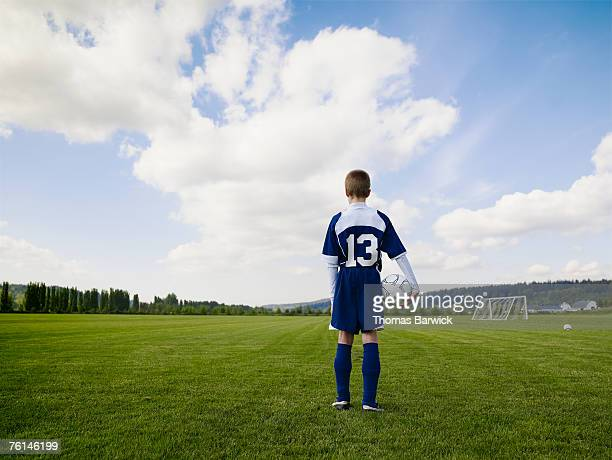 Boy (12-13) standing, holding football, on pitch, rear view