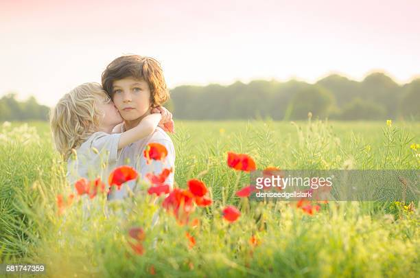 Boy standing in a field kissing his brother