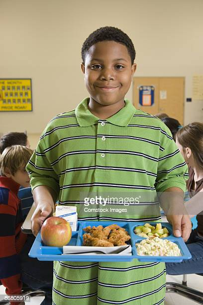 Boy standing in cafeteria with tray