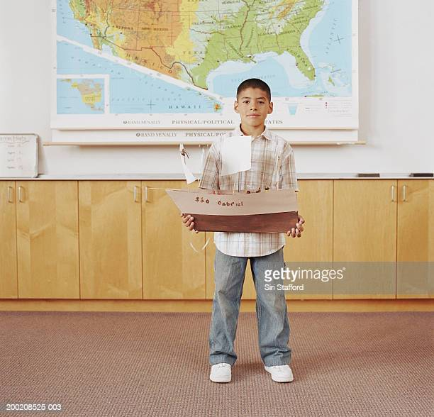 Boy (5-9) standing in classroom, holding model of ship, portrait