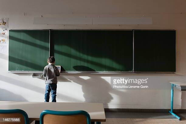 Boy standing in classroom, in front of blackboard, rear view