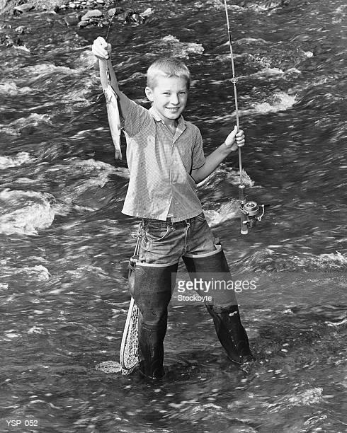 Ragazzo in piedi nel creek, con il pesce al fine di pesca