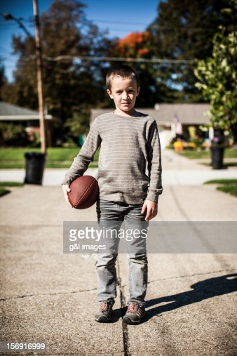 Boy (8yrs) standing in driveway with football : Stock Photo