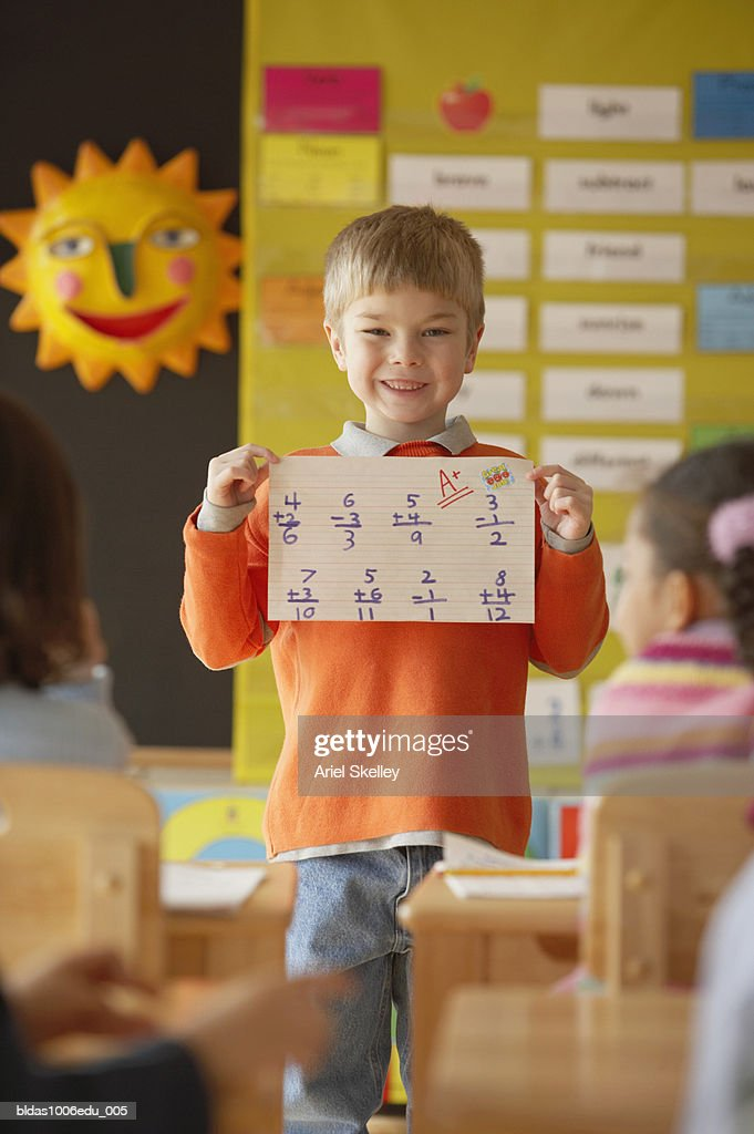 Boy standing in front of a class holding a sheet of paper : Stock Photo
