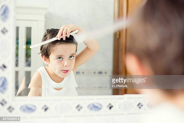 Boy standing in front of a mirror combing his hair
