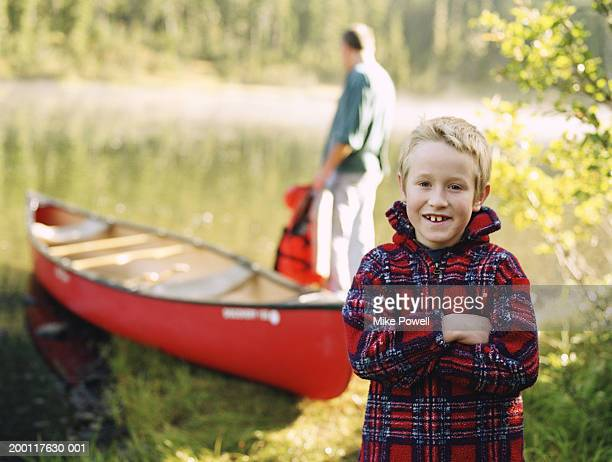 Boy (7-9) standing in front of canoe on lake, father in background
