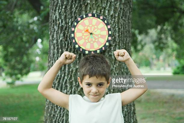 'Boy standing in front of dart board on tree, arms up'