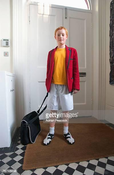 Boy standing in front of door with a bag