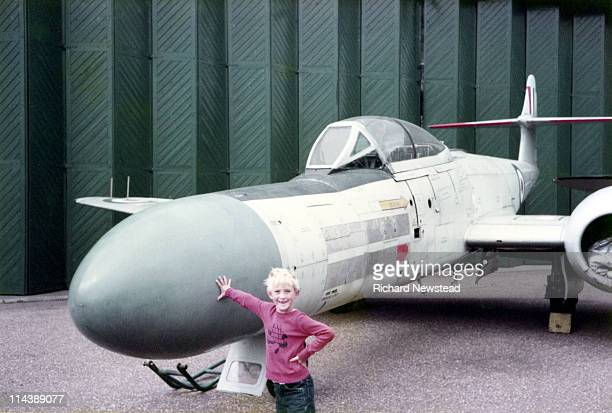 Boy standing in front of fighter jet
