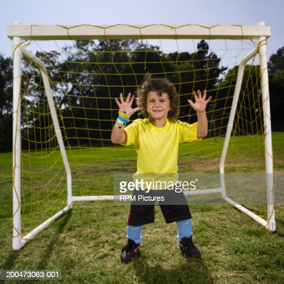 Boy (4-6) standing in front of goal with hands up