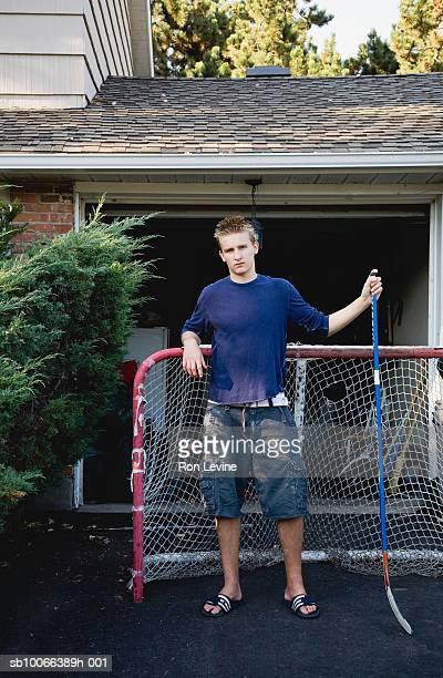 Boy (14-15) standing in front of hockey net in suburban driveway, portrait