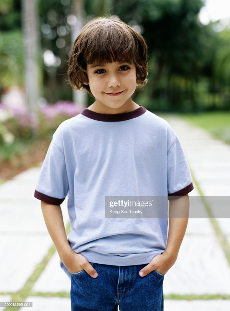 Boy (5-7) standing in garden with hands in pockets, smiling, portrait : Stock Photo