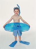 Boy (4-6) standing in rubber ring wearing snorkelling gear, smiling