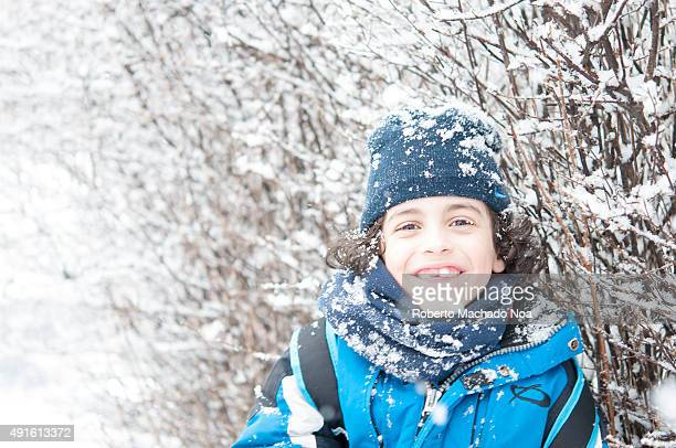 Boy standing in snow and enjoying the Canadian Winter He is wearing a thick blue jacket black pants black gloves and a black hat Trees with snow on...