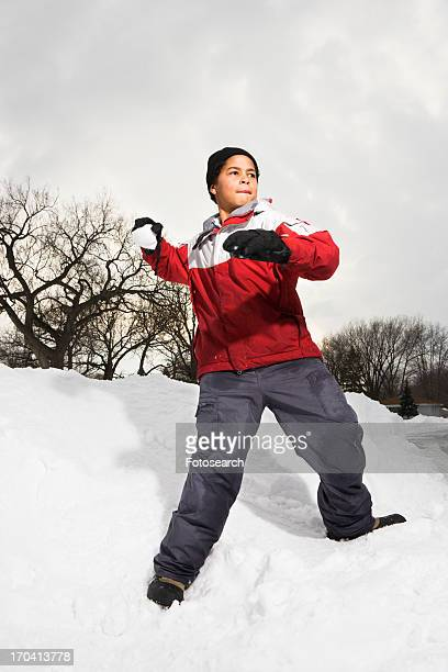 Boy standing in snow throwing snowball