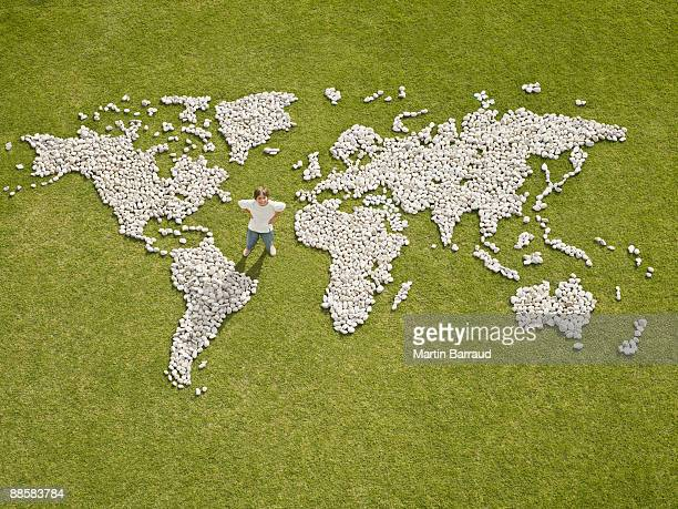 Boy standing in world map made of rocks
