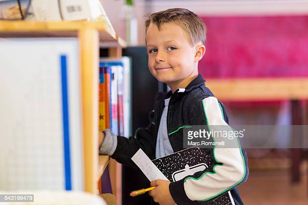 Boy standing near shelf in classroom