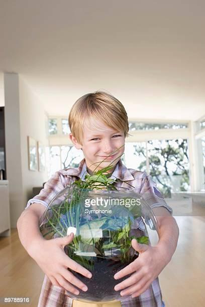 Boy standing next to a homemade terrarium