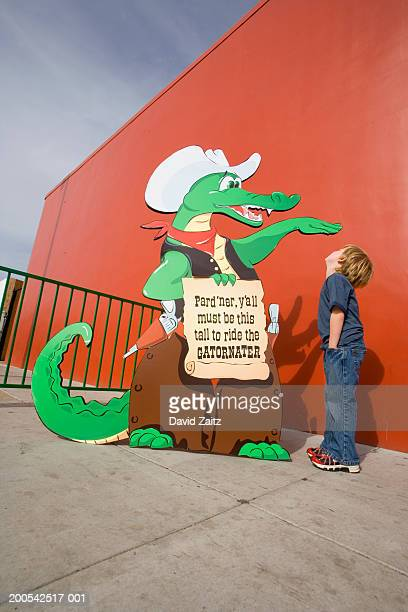 Boy standing next to carnival ride sign indicating height requirement