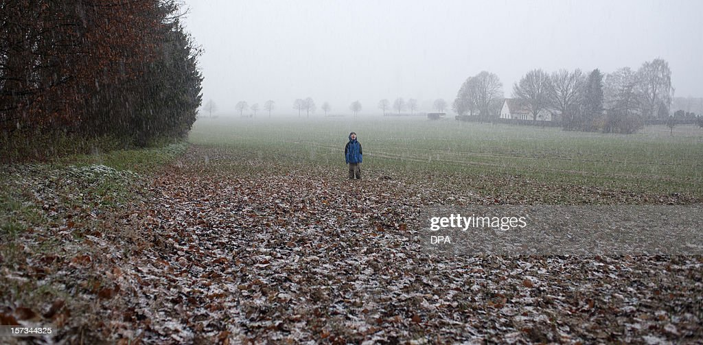 A boy standing on a field plays with falling snowflakes on December 2, 2012 near Benthe, western Germany. First snow of the season fell in the federal state of Lower Saxony. AFP PHOTO / Emily Wabitsch GERMANY OUT