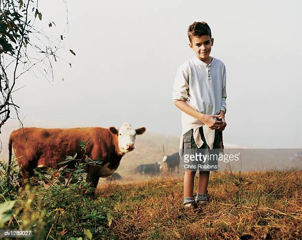 Boy Standing on a Misty Hill With a Cow Standing Behind Him