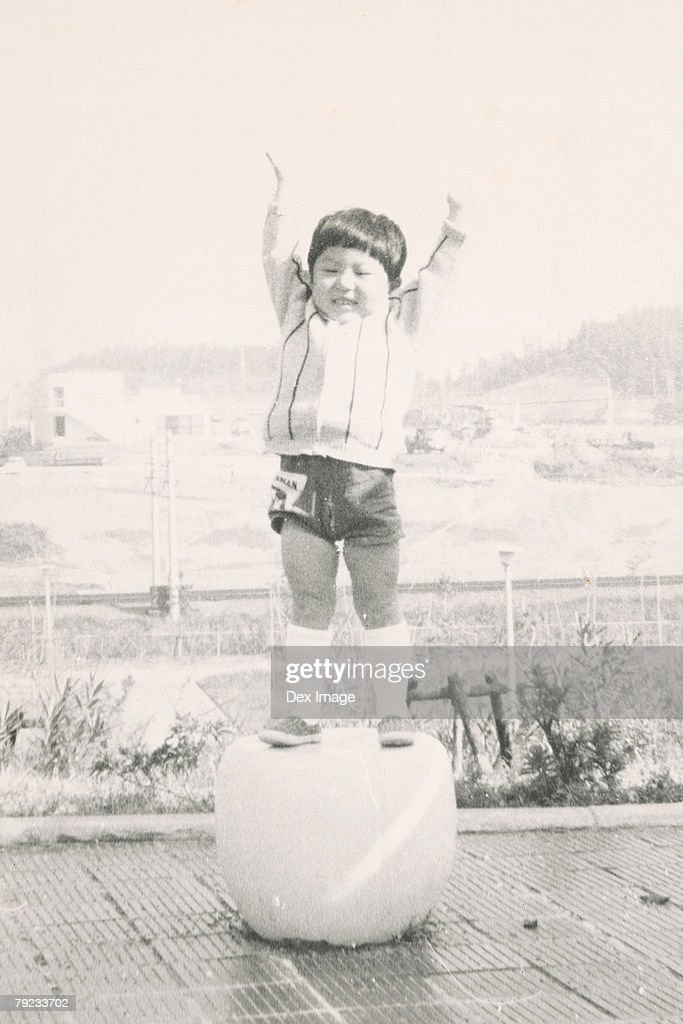 Boy standing on a round seat : Stock Photo