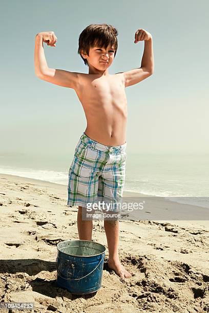 Boy standing on beach flexing muscles