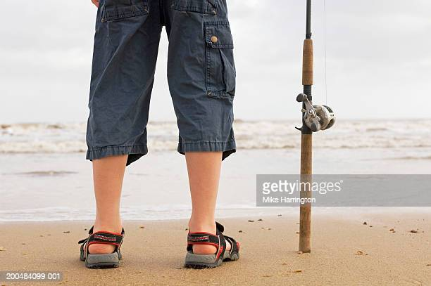 Boy (9-11) standing on beach, holding fishing rod, low section