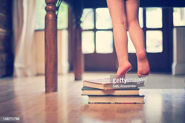 Boy standing on books to reach table