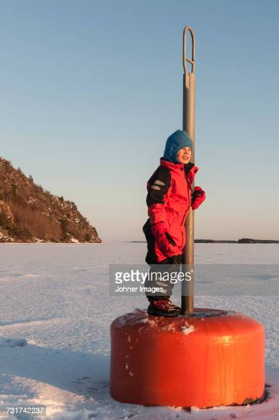 Boy standing on buoy