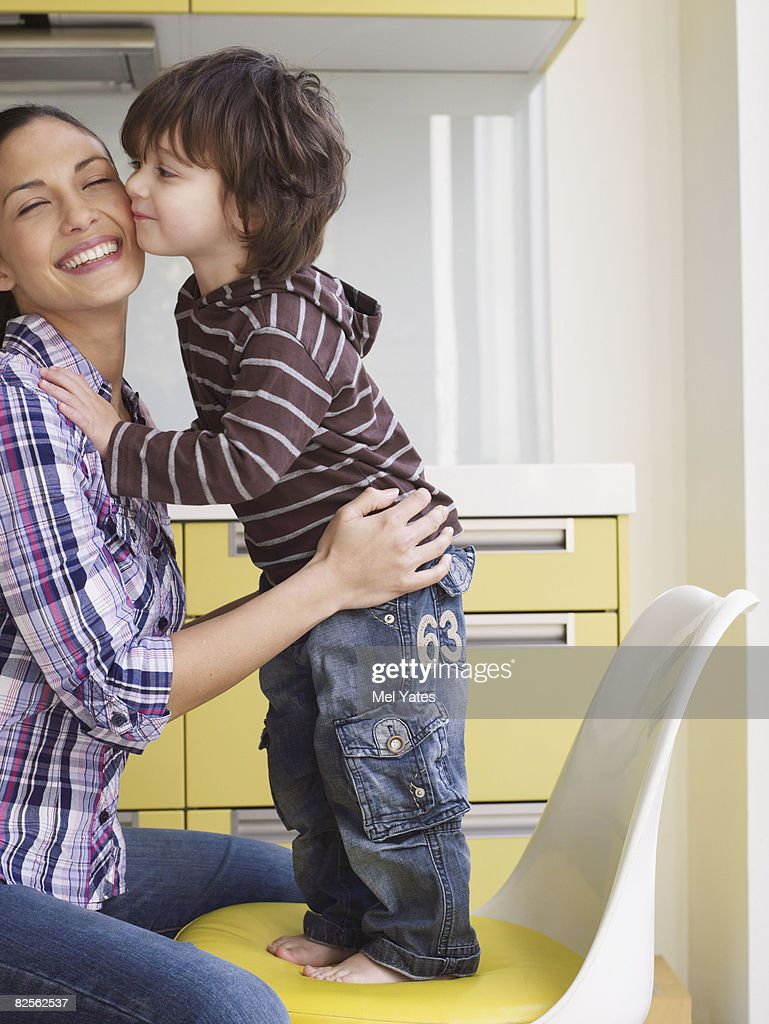 Boy standing on chair kissing mother : Stock Photo