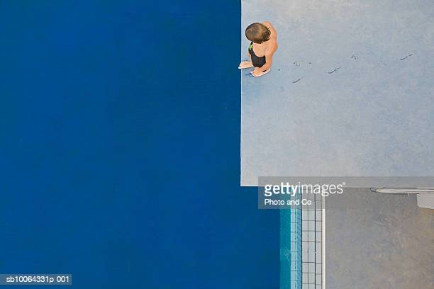 Boy (6-7) standing on diving board, overhead view