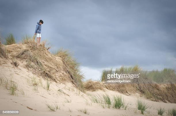 Boy standing on grassy sand dunes, Holkam, Norfolk, England, UK
