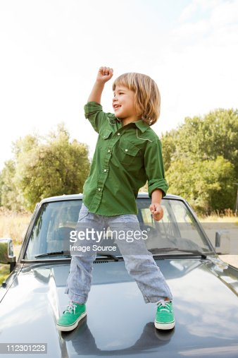 Boy standing on hood of car : Stock Photo