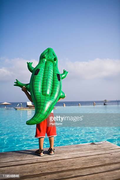 Boy standing on jetty with inflatable