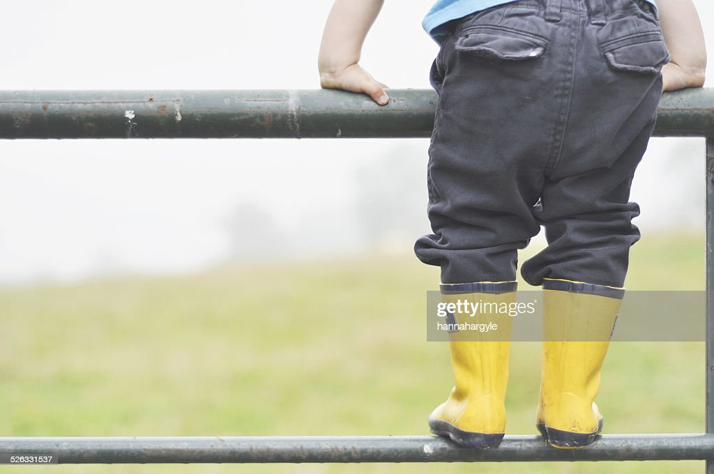 Boy standing on metal fence