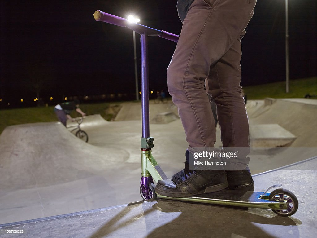 Boy standing on scooter in floodlit skate park. : Stock Photo