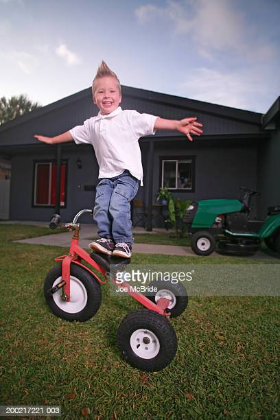 Boy (3-5) standing on seat of tricycle