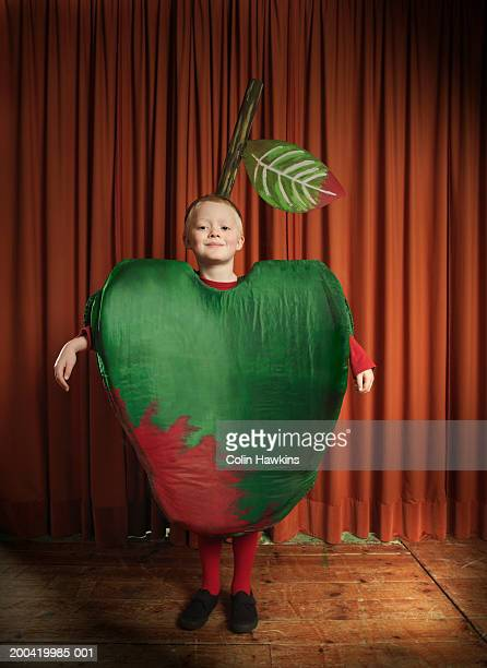 Boy (6-8) standing on stage wearing apple costume, smiling, portrait