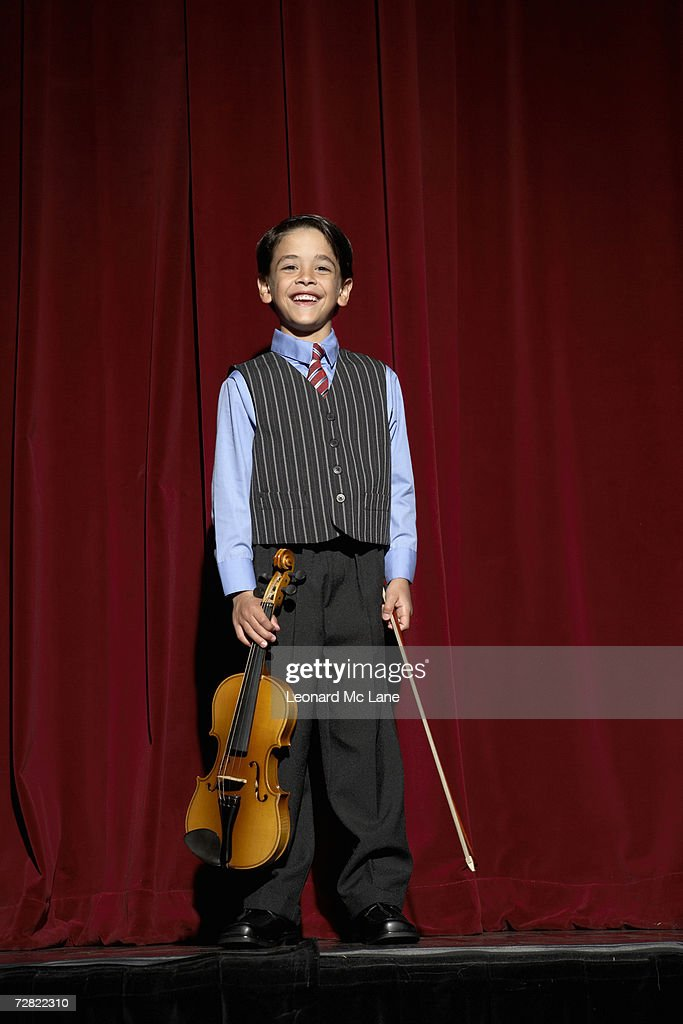 Boy (6-7) standing on stage with violin : Stock Photo