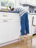 Boy (5-7) standing on stool in kitchen leaning over sink
