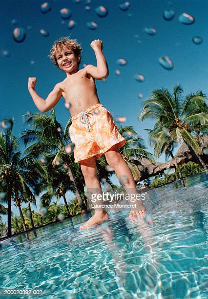 Boy (4-6) standing on submerged wall in swimming pool flexing muscles