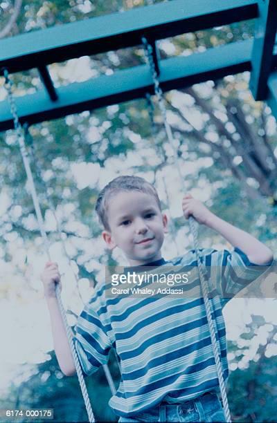 Boy Standing on Swing