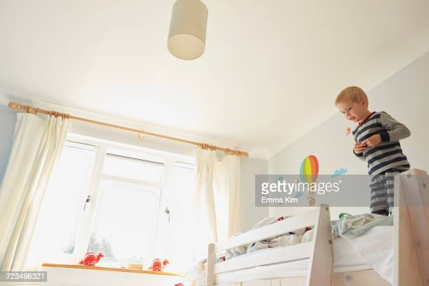 Boy standing on top of bunk bed