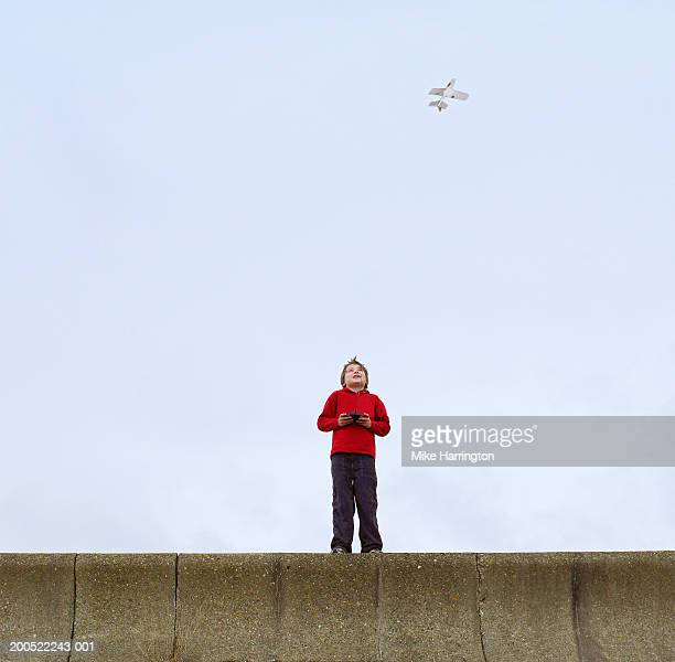 Boy (8-10) standing on wall playing with remote control plane