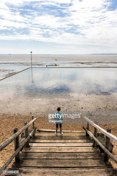 Boy standing on wooden stairs looking at sea, Shoeburyness, Essex, England, UK