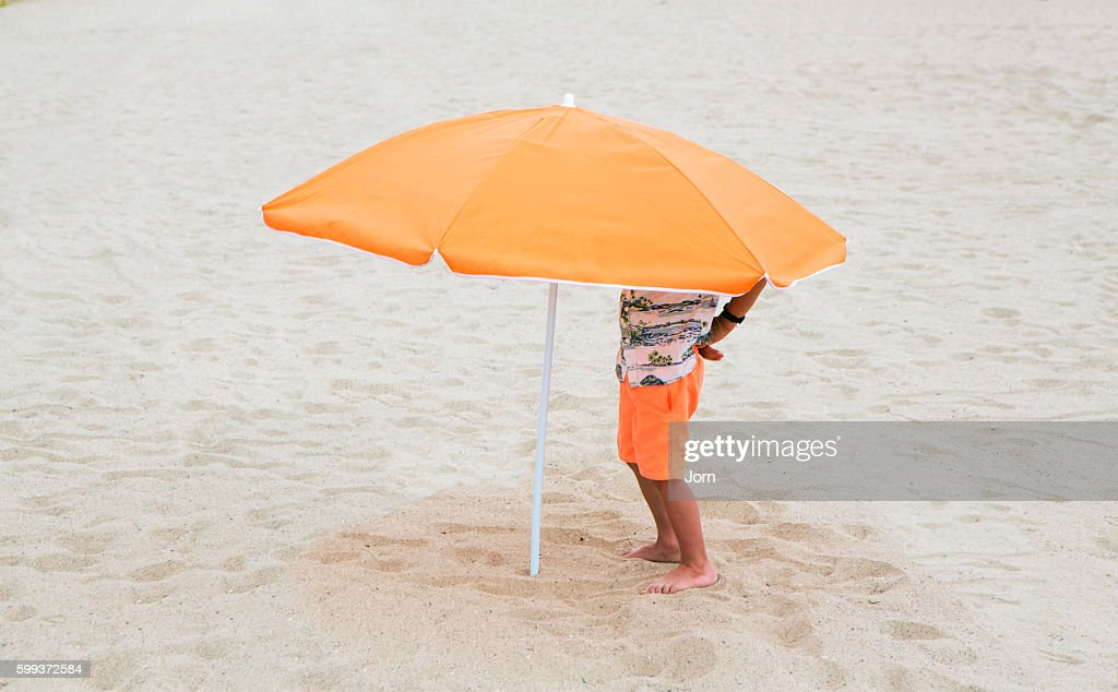 Boy standing under beach umbrella