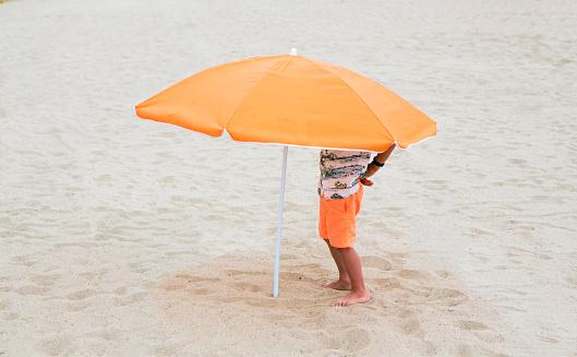 Boy standing under beach umbrella